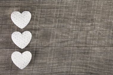 Three white hearts on an old grey brown wooden background.
