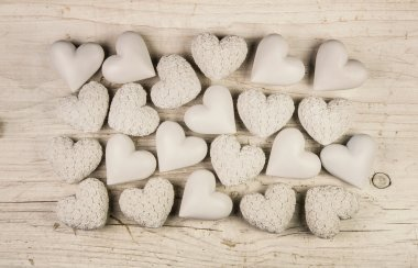 Beige or old white hearts on wooden shabby chic background.