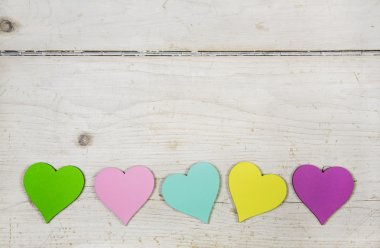 Colorful hearts  on old wooden white shabby chic background.