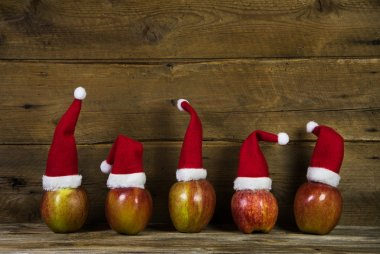 Funny christmas greeting card with five red santa hats on apples