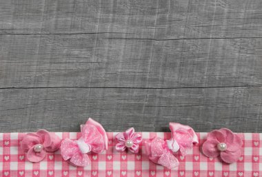 Shabby chic wooden grey background with pink ribbon on white che