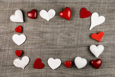 Wooden background with red and white hearts on the frame.