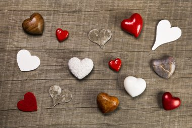 Collection of different red, white and brown hearts on wooden ba