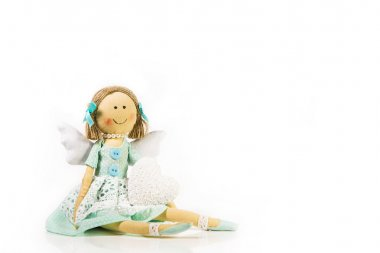 Guardian angel: isolated handmade doll with a white heart in her