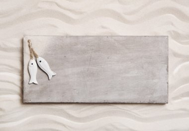 Wooden background with sand and two fishes on an sign like a mes