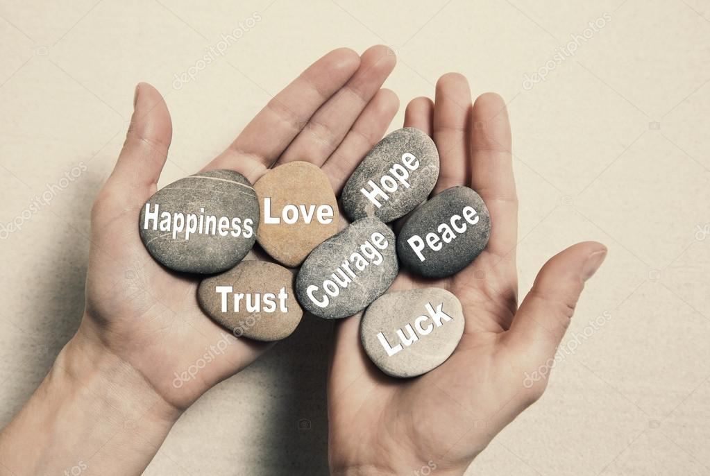 Inner balance concept: hands holding stones with the words happi
