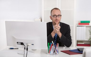 Portrait: Businessman sitting in his office with suit and tie.