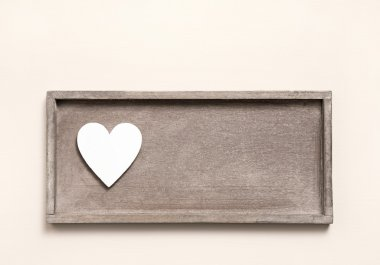 One wooden heart on a sign for a greeting card.
