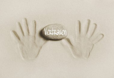 Two hands print in the sand with a stone and the word trust in g