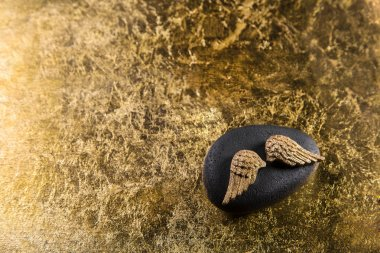 Stone with golden wings for a elegant background.
