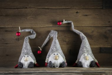 Three handmade imps on wooden background wearing santa hat for c
