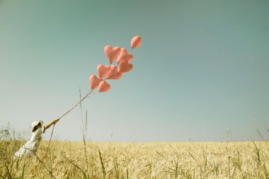 Young romantic girl with red heart balloons walking in a field o