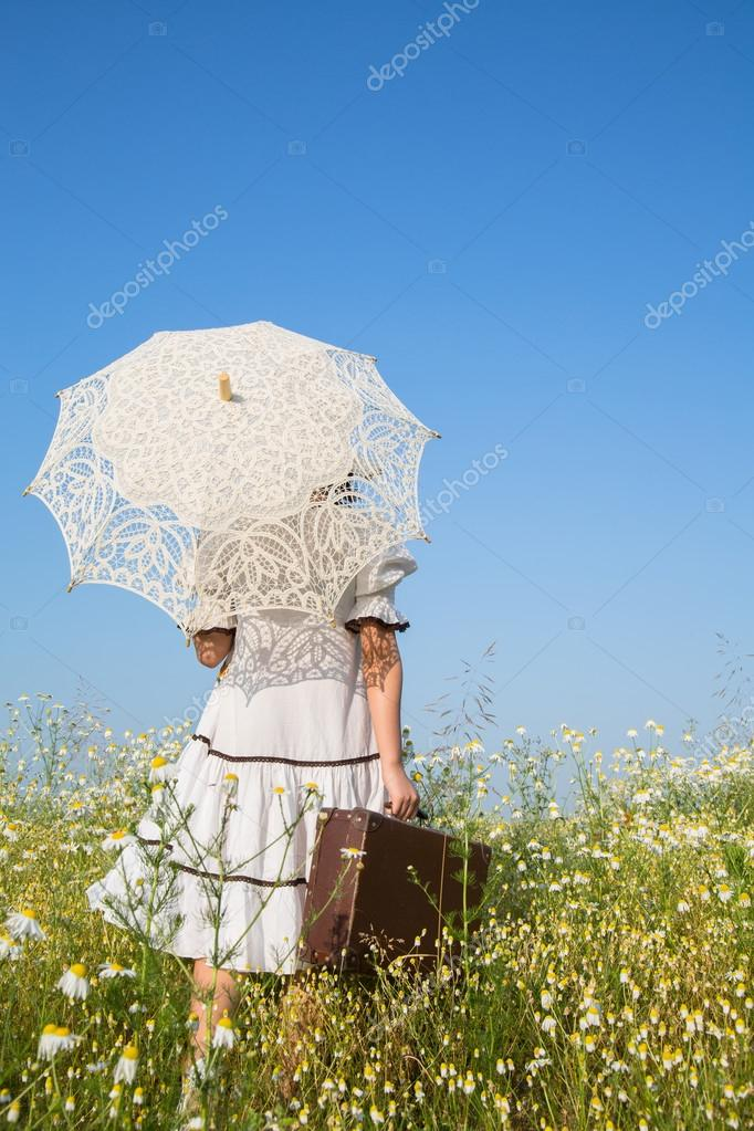 Walking girl in a flowery meadow. Blue sky concept background fo