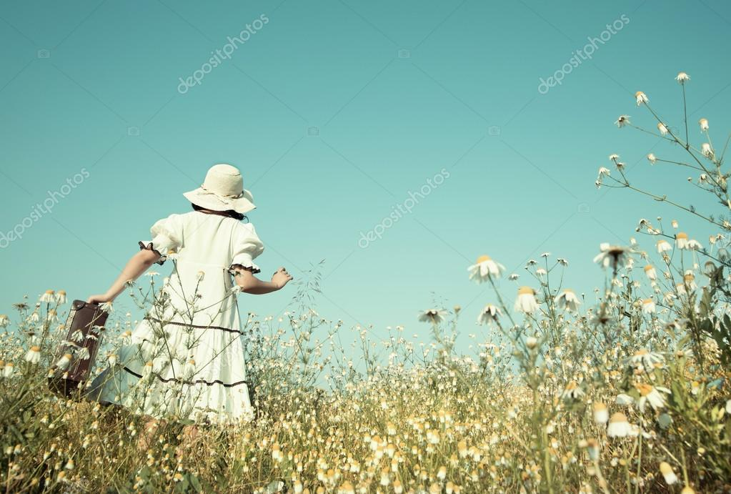 Girl on the way to her future walking in a flowery meadow with h