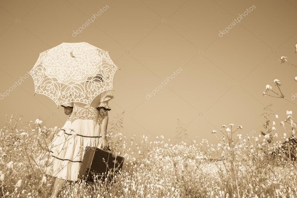 Nostalgic old photo in sepia color. Girl with her umbrella walki