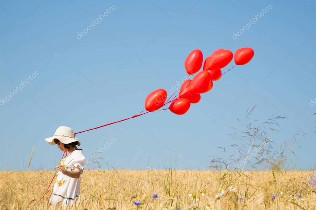 Child with flying red heart balloons on the blue sky background.