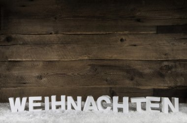 The word christmas in white german letters on wooden old rustic