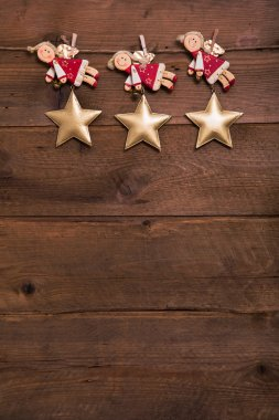 Three red and golden Christmas angels on old wooden background f