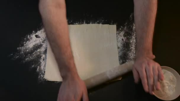Hand Man Throws a Black Table Rolls Raw Dough