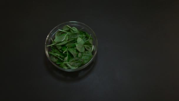 Čerstvý špenát ve skleněné mísy na černém stole