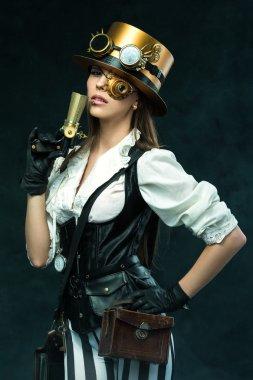 Portrait of a beautiful steampunk woman holding a gun