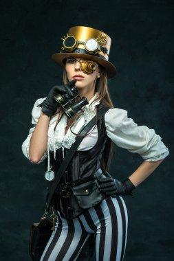 Portrait of a beautiful steampunk girl with binoculars