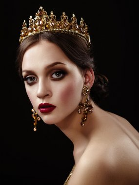 Beautiful brunette girl with a golden crown, earrings and profes