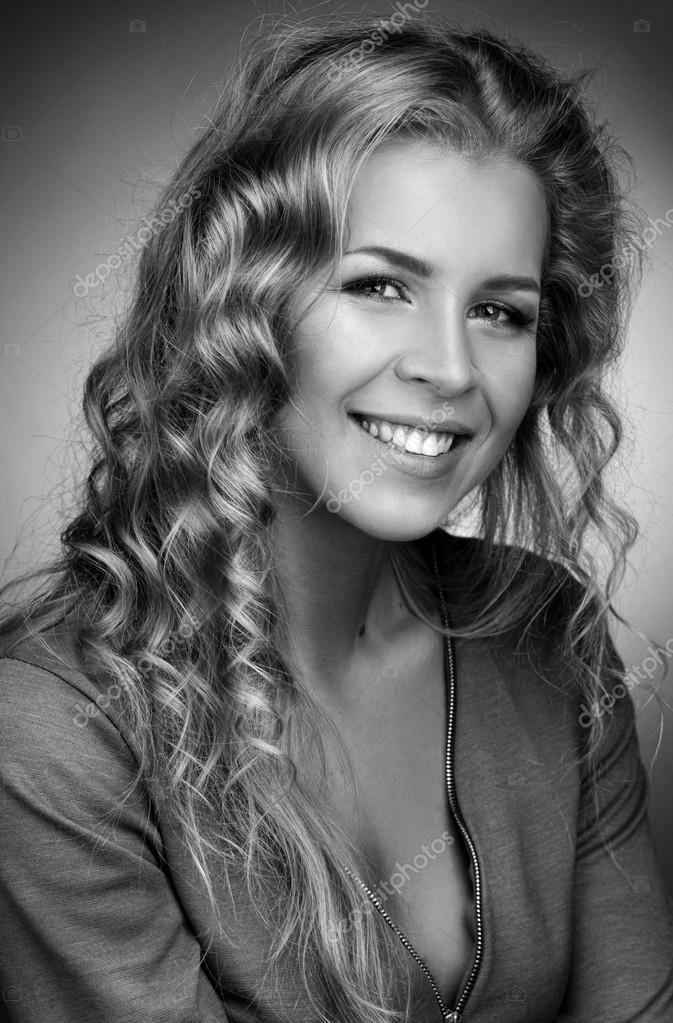 Smiling blonde with long curly hair.