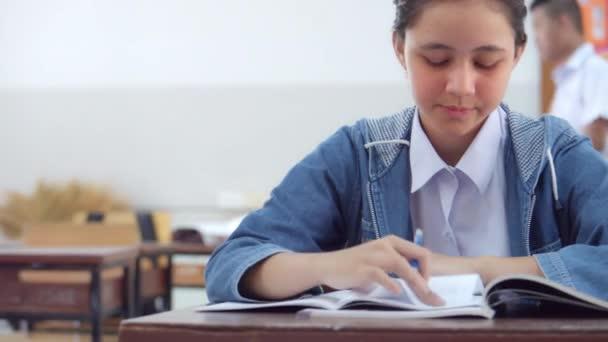 Roztomilé dospívající středoškolačka v bílé školní uniformě na sobě džínový svetr sedí ve třídě dělá práci vykonávanou učitelem, zatímco její přátelé procházeli kolem.