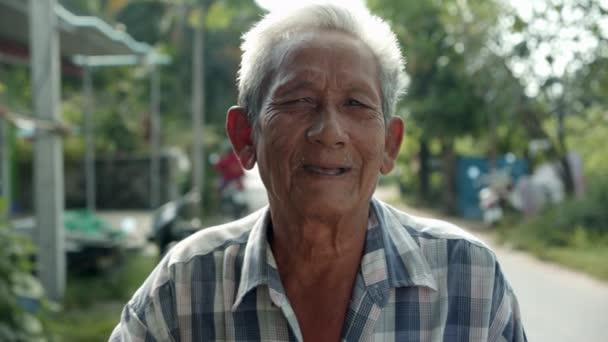Lassú mozgású jelenet a fehér hajú, szegény ázsiai öregemberről, több mint hetvenen állnak boldogan mosolyogva a falu útszélén reggel..