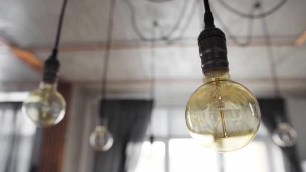 Velké vinobraní žárovky visící v moderní kuchyni. Dekorativní starožitné žárovky s rovným drátem. Neefektivní žárovky ztrácejí elektřinu. Teplo bílé, stmívatelné, E27