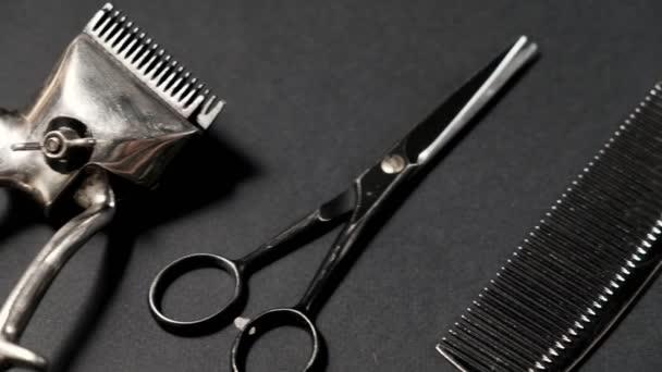 Egy fekete felületen régi borbély szerszámok vannak. Vintage manuális hajvágó, fésű, borotva, fodrász olló. Fekete monokróm. Közelkép. Borbélyüzlet háttere. kontraszt árnyékok. csúsztatás. 4k.