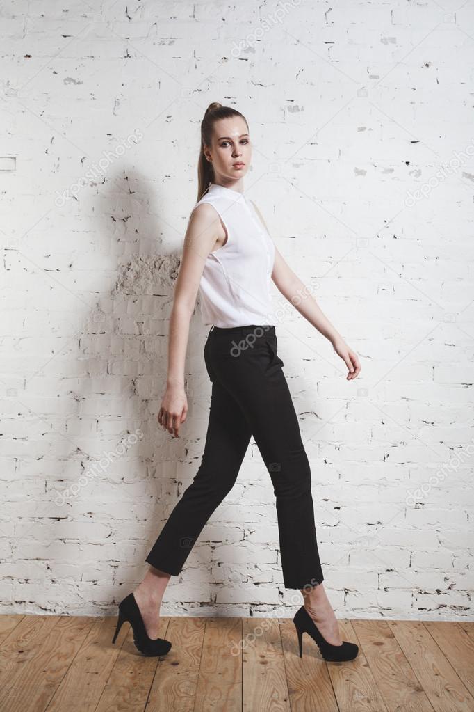 578dc206a4 Modelka w czarne spodnie i biała bluzka pozowanie na białym tle. Portret  kobiety