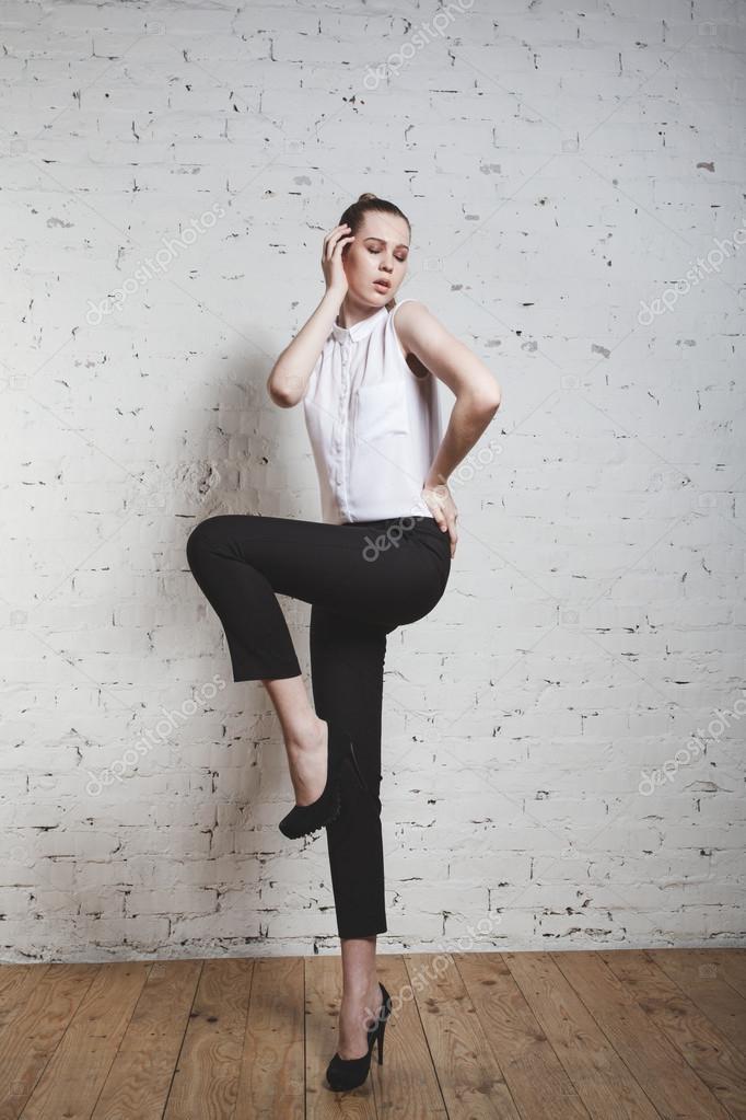 2f0b5e6b16 Modelka w czarne spodnie i biała bluzka pozowanie na whi– obraz stockowy
