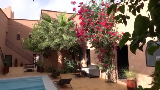 Marokko, Marrakesch - Oktober 2019: Schwimmbad im Innenhof im traditionellen marokkanischen Riad mit Lehmhäusern in arabischem Design und Bäumen mit Blumen