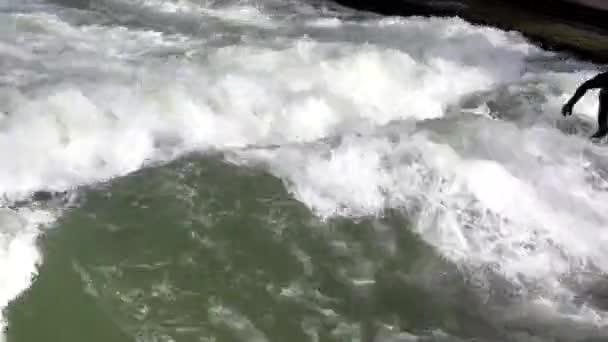 MÜNCHEN, DEUTSCHLAND - MÄRZ 2020: Profi-Surfer im schwarzen Taucheranzug surft im Winter auf dem Eisbach im Englischen Garten
