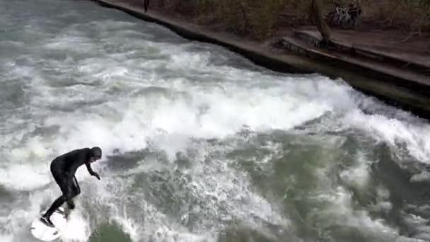 MÜNCHEN - MÄRZ 2020: Profi-Surferin im schwarzen Taucheranzug surft im Winter auf dem Eisbach im Englischen Garten