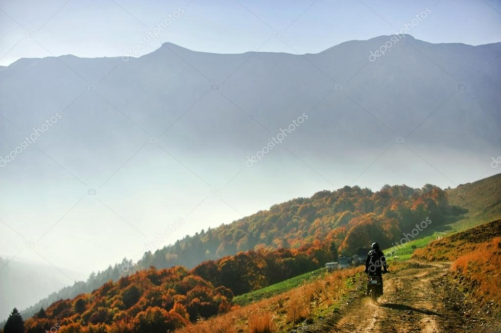 Motorcycle on a mountain dirt road in autumn