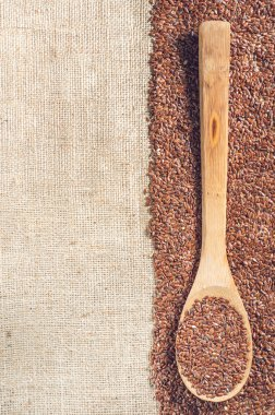 flax seeds with a wooden spoon on burlap background