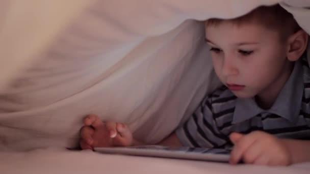 Chlapče, ležící pod deku a sleduje kreslené na dotyková podložka