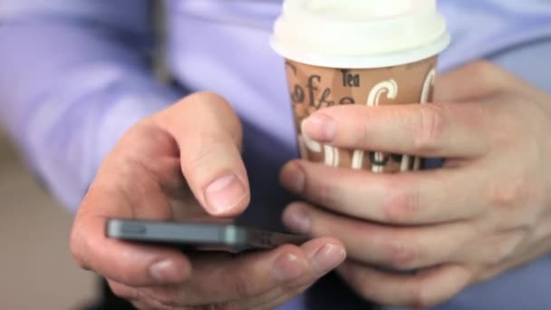 close-up mans hands using mobile phone touchscreen and cofee