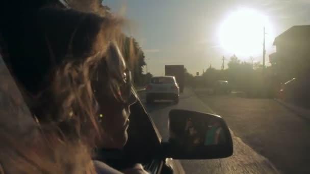 Wind weht durch Mädchenhaare in einem Auto mit Familie. Sonnenuntergang