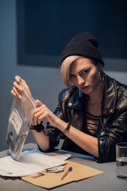 Sorgu odasında çantasında silahla poz veren genç ve güzel bir suçlu kız.