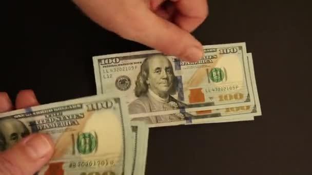 Ruce počítající dolary na černém povrchu
