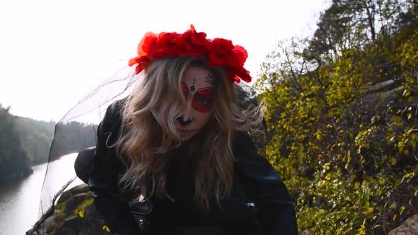 Halloween-Filmmaterial. Schöner Halloween Make-up Stil. Blondes Model trägt Zuckerschädel-Make-up mit roten Blumen. Santa-Muerte-Konzept