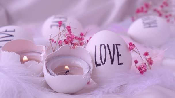 Aufnahmen vom Entzünden einer Kerze in Ostereiern. Worte, die mit Stift gezeichnet wurden. Liebe. Gemütliche Wohnkultur, brennende Kerzen. Valentinstag