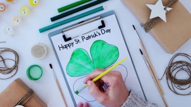 Ženské ruce malovat blahopřání St Patricks den. Dárkový nápad, dekorační řemeslo. DIY. Udělej si to sám. Lovci, štětec a nátěr.