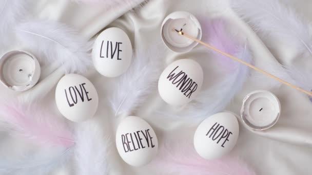 Aufnahmen vom Entzünden einer Kerze in Ostereiern. Worte, die mit Stift gezeichnet wurden. Ansicht von oben. Love Live Believe Wonder Hope. Gemütliche Wohnkultur, brennende Kerzen