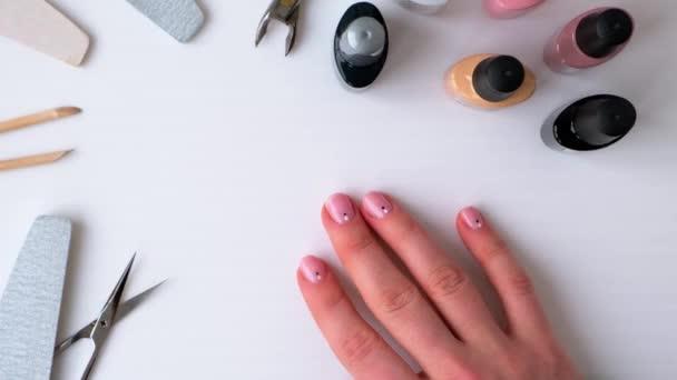 Ženské ruce ukazují manikúru. Reklama na nehty, salóny krásy, práce doma s nehty. Péče o nehty, péče o sebe. Ženská manikúra. Udělej si manikúru sám