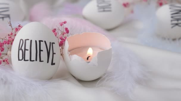 Aufnahmen vom Entzünden einer Kerze in Ostereiern. Worte, die mit Stift gezeichnet wurden. Glauben Sie mir. Gemütliche Wohnkultur, brennende Kerzen